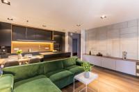 Zelená rohová sedačka v modernej obývačke s kuchyňou