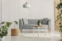 Sivá pohovka vo svetlej škandinávskej obývačke