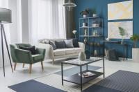 Svetlá pohovka a kovové regály s modrou stenou