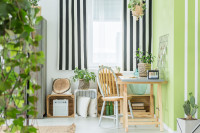 Drevený písací stôl v zeleno-bielej pracovni s rastlinami