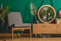 Sivá pohovka a okrúhle zrkadlo v zelenej retro obývačke