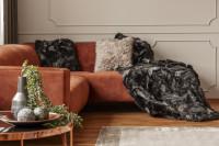 Hnedá rohová pohovka s huňatou dekou a vankúšmi