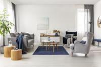 Sivá pohovka a kreslo ušiak v obývačke s modrými doplnkami