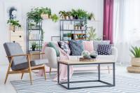 Retro kreslo a svetlá pohovka v škandinávskej obývačke