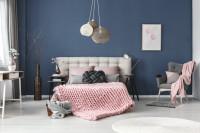 Spálňa s modrou stenou a ružovými textilnými doplnkami