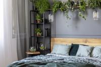 Drevená manželská posteľ v kontraste so sivou stenou
