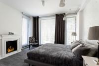 Sivá posteľ a závesy v priestrannej modernej spálni