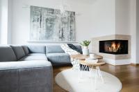 Rohová pohovka a sada stolíkov v obývačke s krbom