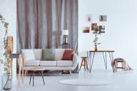 Biela pohovka a subtílny drevený nábytok