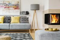 Pohovka s dekoračnými vankúšmi a stojanová lampa v škandinávskej obývačke s rohovým krbom