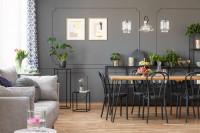 Dlhý jedálenský stôl a drevené stoličky v sivej jedálni