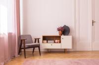 Sivé retro kreslo a nízka komoda v obývačke s ružovými závesmi