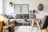 Sivá rohová pohovka s čiernobielymi dekoráciami