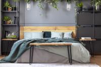 Drevená manželská posteľ a elegantné kovové regále v modernej spálni