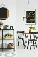 Čierny regál a jedálenský stôl s drevenými stoličkami
