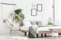 Závesné kreslo a drevená posteľ vo svetlej spálni