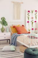 Biela kovová posteľ a kvetinové dekorácie
