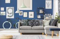 Modrá stena s obrazmi a sivá rohová pohovka