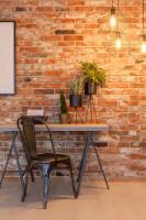 Písací stôl a stolička v industriálnej pracovni s tehlovou stenou
