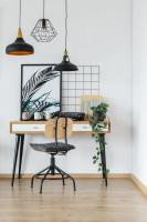 Drevený písací stôl a čierne lampy v škandinávskej pracovni