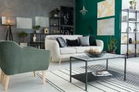 Svetlá retro pohovka v kontraste so zelenou stenou
