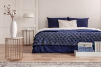 Manželská posteľ s modrými obliečkami a odkladacie stolíky