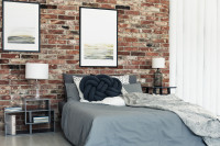 Manželská posteľ v industriálnej spálni s tehlovou stenou