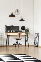 Písací stôl a stolička v pracovni s industriálnymi lampami