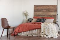 Drevená posteľ s červenými obliečkami a pletenou dekou
