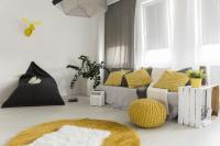Pohovka so žltými vankúšmi a čierny sedací vak