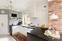 Biela kuchynská linka s čiernou pracovnou doskou v malej kuchyni s tehlovou stenou