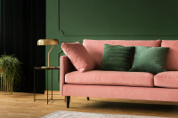Ružová pohovka v kombinácii so zelenou stenou a dekoračnými vankúšmi