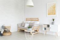 Okrúhly stolík a pohovka v bielej škandinávskej obývačke