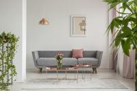 Sivá pohovka a medené stolíky v elegantnej obývačke