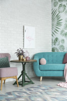 Modrá retro pohovka v obývačke s bielou tehlovou stenou