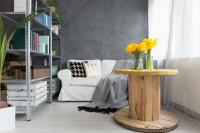Biela pohovka a kovový regále v malej obývačke so sivou stenou