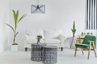 Zelené kreslo a dvojmiestna pohovka vo svetlej obývačke