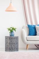 Modrá váza na kovovom stolíku vo svetlej obývačke