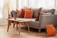 Pohodlná sivá pohovka s dekoračnými vankúšmi v jesenných farbách