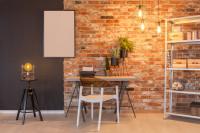 Písací stôl v industriálnej pracovni s tehlovou stenou