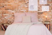 Manželská posteľ s ružovými obliečkami v spálni s tehlovou stenou