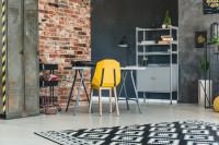 Kovový písací stôl a žltá stolička v industriálnej pracovni