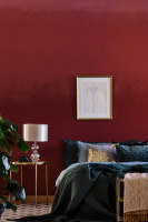 Posteľ a zlatý stolík v spálni s bordovou stenou