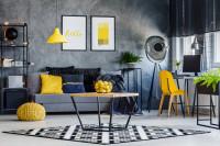 Pohovka v sivej industriálnej obývačke so žltými doplnkami