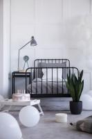 Čierna kovová posteľ v bielo-sivej študentskej izbe