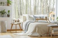 Biela manželská posteľ v škandinávskej spálni s prírodnými doplnkami
