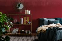 Posteľ a zlaté doplnky v bordovej glamour spálni