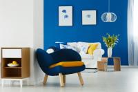 Dizajnové kreslo v obývačke s modrou stenou