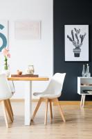 Drevený stôl a plastové stoličky v čierno-bielej jedálni