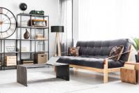 Čierna pohovka a kovové regále v industriálnej obývačke